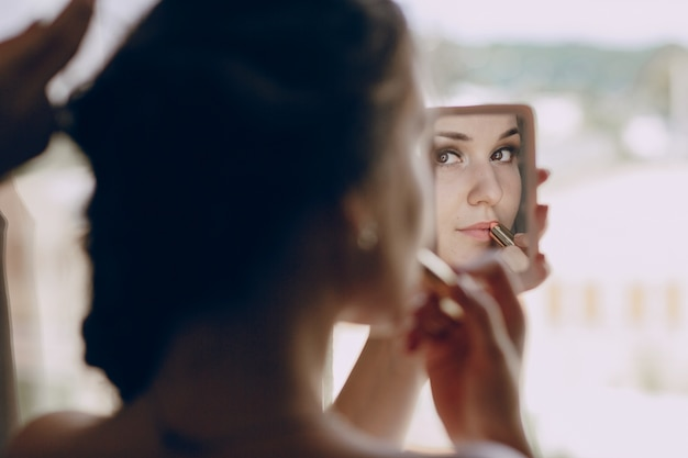 Bride making  up in a small mirror Free Photo