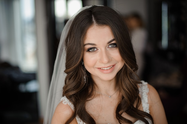 Bride morning preparation. beautiful and smiling bride in a white veil Premium Photo