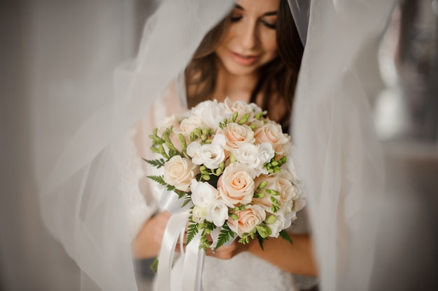 Bride morning preparation. portrait of a lovely bride in a white veil with a wedding bouquet Premium Photo
