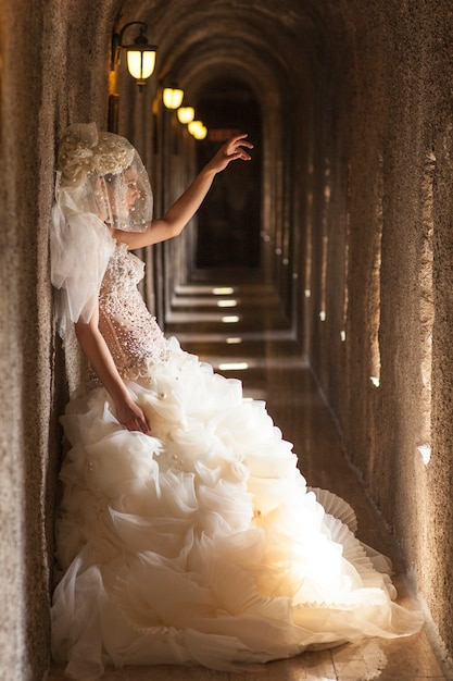Bride next to the wal with raised hand Free Photo