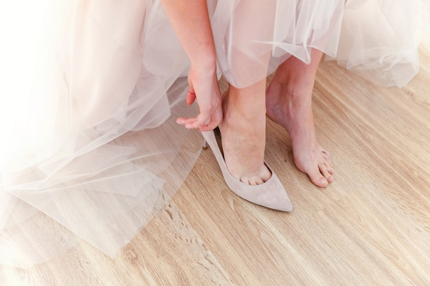 Bride prepare for ceremony wearing beautiful shoes on foot in wedding day Premium Photo