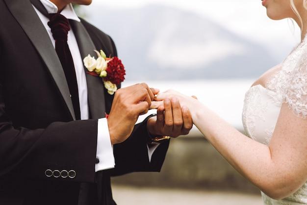 Bride puts wedding ring on groom's finger Free Photo