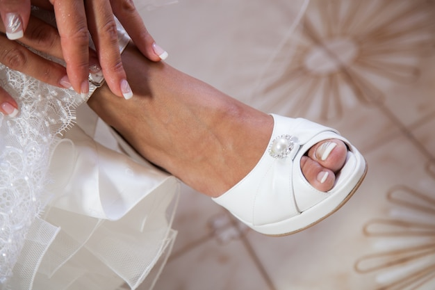 Bride putting on her white wedding shoes Premium Photo
