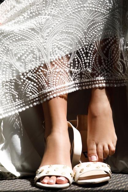 Bride's tender feet on elegant shoes Free Photo