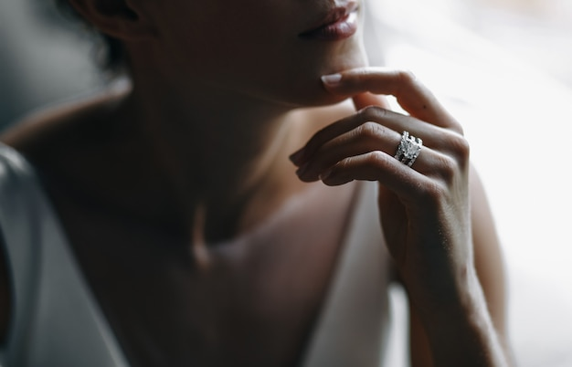 Bride's tender fingers touch her chin Free Photo