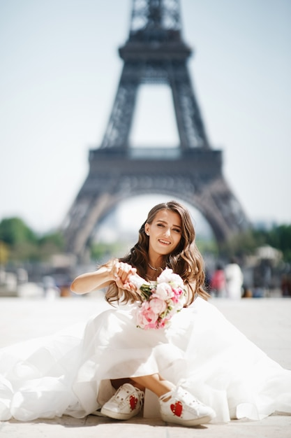 Bride sits in snickers before the eiffel tower in paris Free Photo