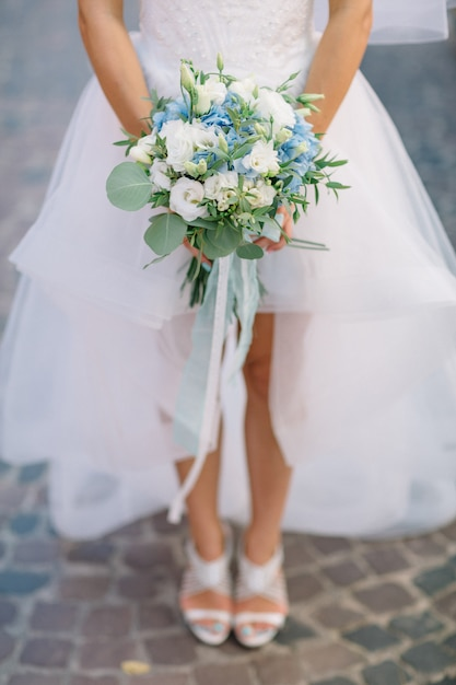 Bride walks on the street with blue wedding bouquet Free Photo