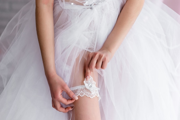 Bride wearing wedding garter. a woman demonstrates her sexy legs Premium Photo