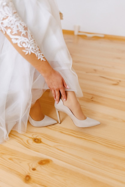 The bride wears shoes on a wedding morning Premium Photo