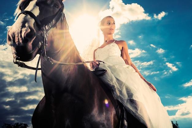Bride in wedding dress riding a horse, backlit Premium Photo
