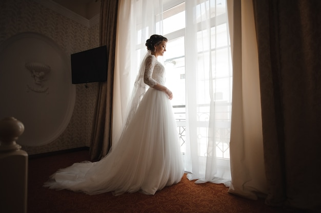 Bride in a white lace dress with a plume stands against the window Premium Photo