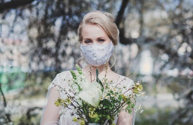 防護マスクに花束を持つ花嫁 Premium写真