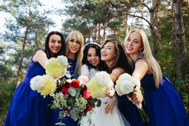 Bride with bridesmaids holding bouquets posing Free Photo