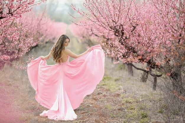 咲く庭の花bride。長いピンクのドレスを着た女性。 Premium写真
