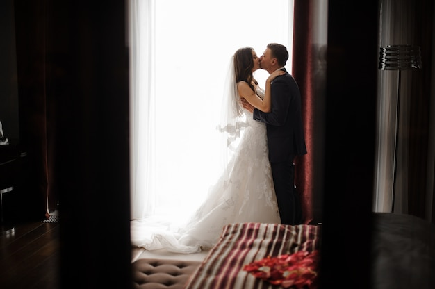 Bridegroom and bride in long dress are kissing near the window Premium Photo