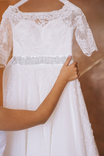 Bridesmaid buttoning the dress on bride, details of beautiful lace wedding dress Premium Photo
