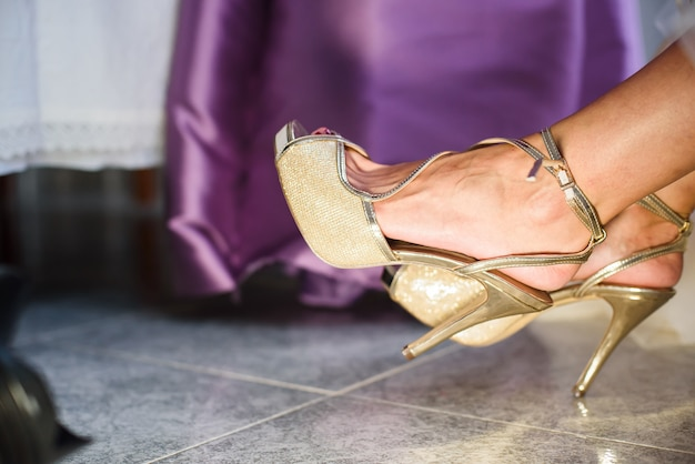 Bridesmaid helping young bride to put on the shoes before the wedding ceremony. Premium Photo
