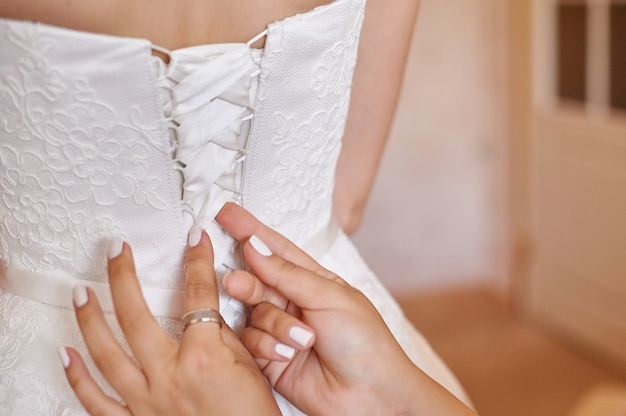 Bridesmaid helps bride to dress in the morning Premium Photo
