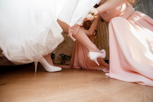 The bridesmaid helps her to wear a dressing-jewelry on her leg. Premium Photo