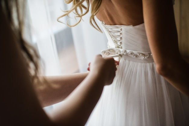 Bridesmaid helps to wear a wedding dress Premium Photo