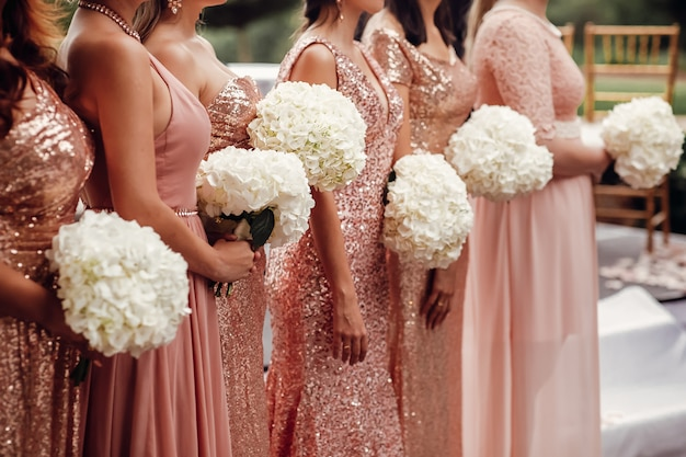 Bridesmaids in pink dresses stand with white flower bouquets in Free Photo