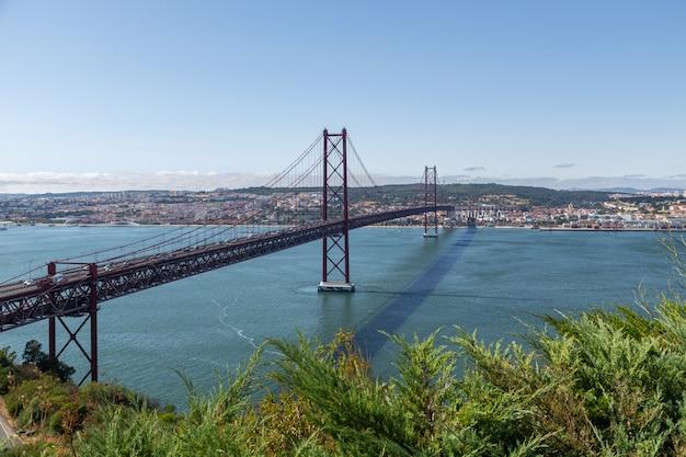 移動中の車でtejo川沿いのリスボンの橋。 Premium写真