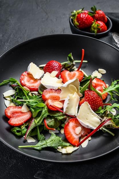 Салат из сыра бри с клубникой, орехами, мангольдом и рукколой. черный фон. вид сверху. Premium Фотографии
