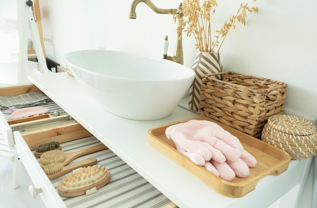 Premium Photo | Bright bathroom. drawn out drawers with massagers and  brushes. wicker baskets and sink.