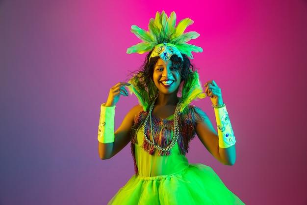 선명한. 네온 그라데이션 벽에 춤 깃털을 가진 카니발, 세련 된 무도회 의상에서 아름 다운 젊은 여자. 휴일 축하, 축제 시간, 댄스, 파티, 재미의 개념. 무료 사진