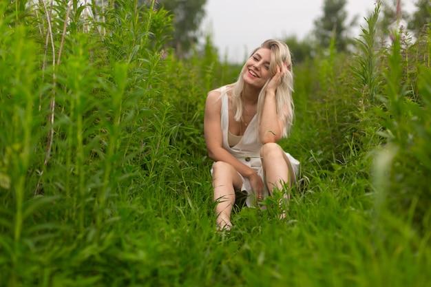 Блондинка на лугу среди травы