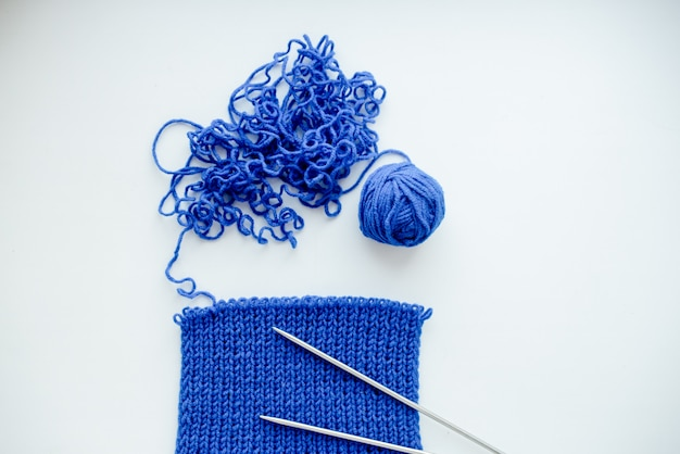 Bright blue scarf with knitting needles. on whitebackground.hobby and free time concept.  top horizontal view Premium Photo