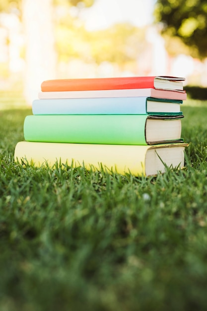 Bright book stack on green grass Free Photo