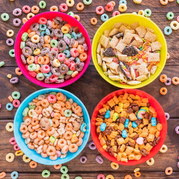 Bright bowls with cereals on wooden table Free Photo