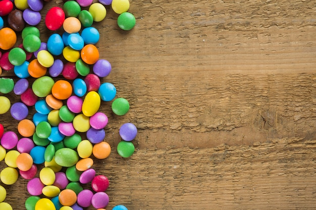Bright candy buttons on lumber background Free Photo
