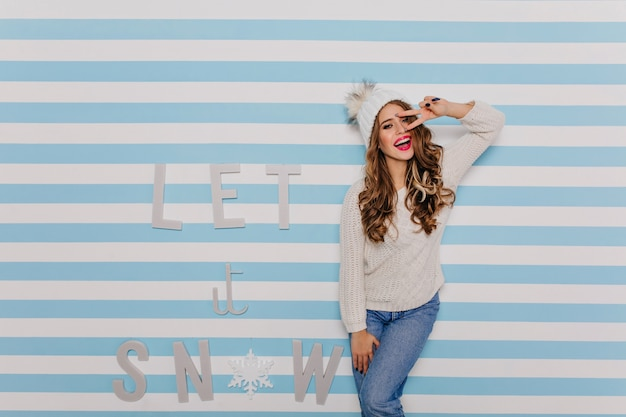 暖かいウールのセーターと白いニット帽をかぶった明るく陽気で魅力的な女性は、見て楽しんでいます。 無料写真