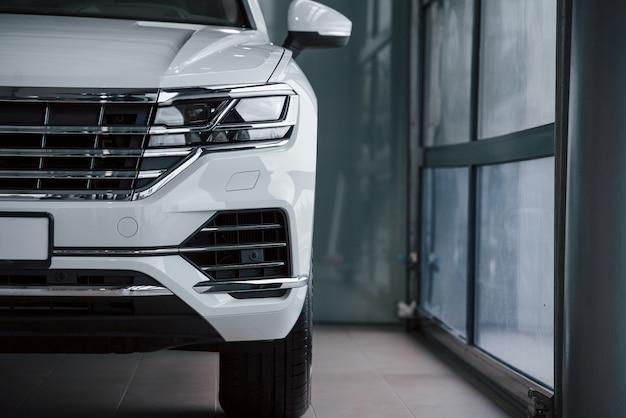 Яркий цвет. частичный вид современного роскошного белого автомобиля, припаркованного в помещении в дневное время Бесплатные Фотографии