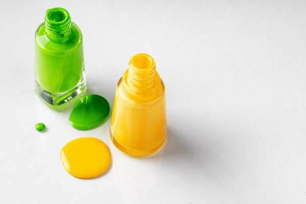 白の滴下と明るい色のマニキュアボトル Premium写真