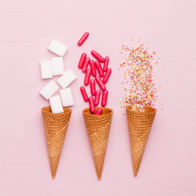 Bright composition of sugar dressing red pills and ice cream cones Free Photo