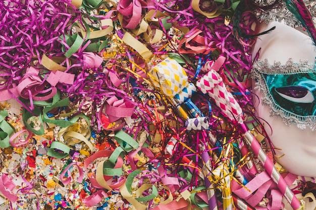Bright confetti and serpentine with mask Free Photo