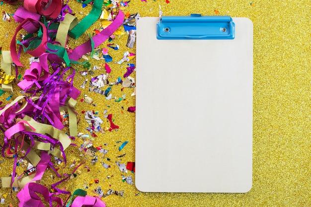 Bright confetti near clipboard Free Photo