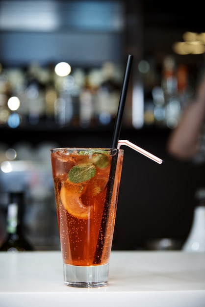 A bright cool cocktail with bubbles and straws on a dark background of a blurred bar. Premium Photo