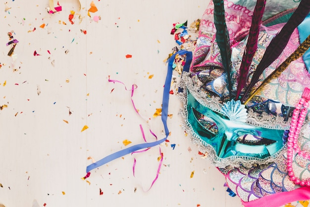 Bright costume with mask in confetti Free Photo