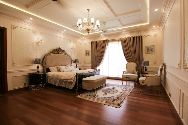 Bright and cozy luxury bedroom with classic design, large window and sill with soft seats and cushion Premium Photo