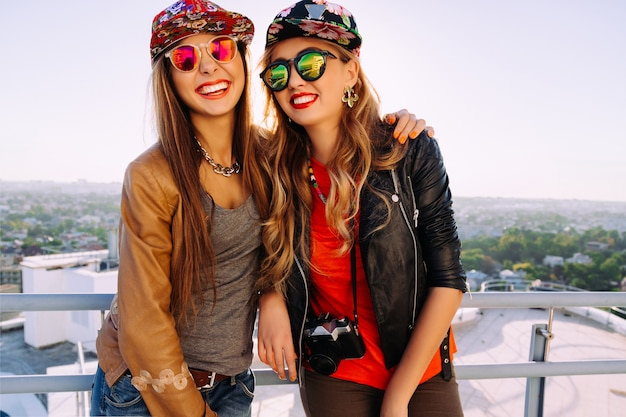 スタイリッシュな盗品の帽子、革のジャケットとサングラスを身に着けて、笑いながら一緒に楽しんでいる2人のかわいい姉妹の明るいファッションアウトドアライフスタイルの肖像画。屋根でポーズをとる最高の悪鬼 無料写真