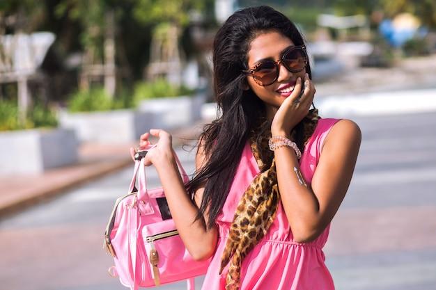 Ritratto di moda brillante di splendida sensuale bruna asiatica ragazza tailandese in posa a santorini, indossando sciarpa leopardo alla moda e occhiali da sole, mini abito rosa di seta, viaggiando da solo. Foto Gratuite
