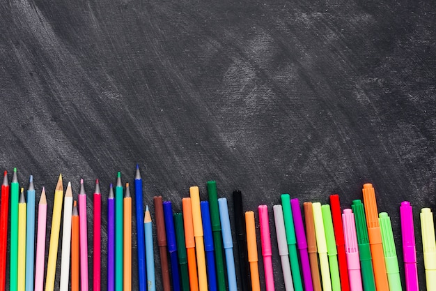 Bright felt pens and pencils at bottom of dark background Free Photo