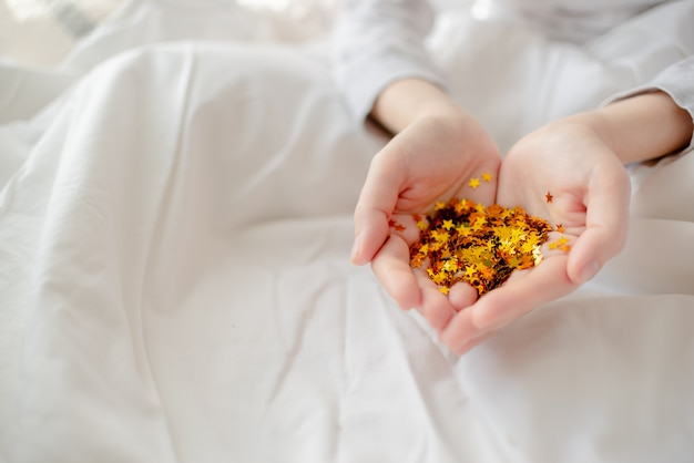 Bright festive golden confetti star sparkles woman hand. creative conceptual christmas holiday birthday party top view Premium Photo