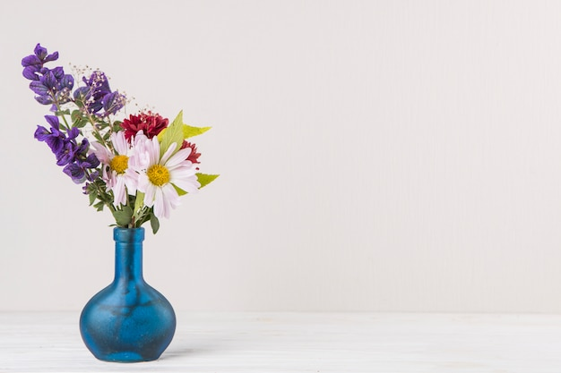 Bright flowers in blue vase on table Free Photo