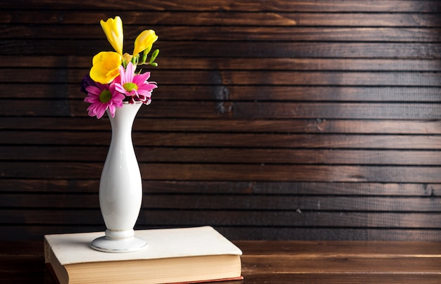 Bright flowers in vase on book Free Photo
