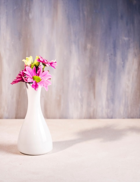 Bright flowers in white vase on table Free Photo